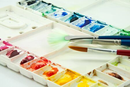 used watercolor palette and paintbrush Stock Photo