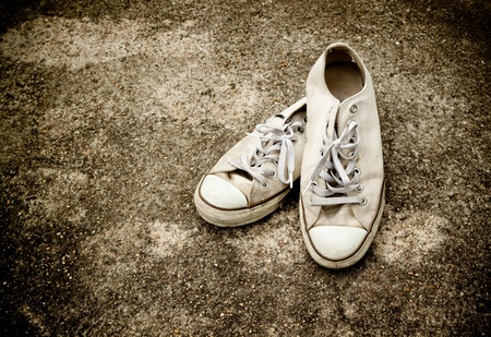 sneakers: pair of old sneakers on grungy background