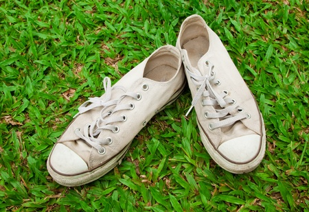 pair of old sneakers on green background