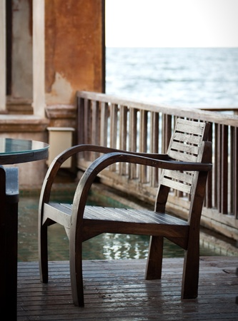 brown wood chair on terrace beside the sea