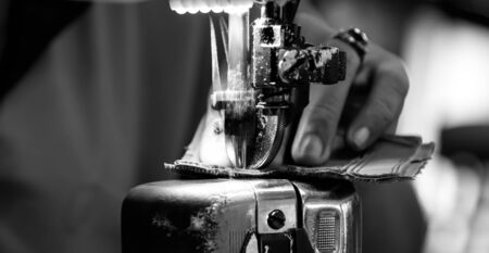 stitching machine: motion blur of worker stitching on footwear component