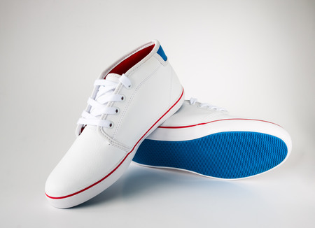 pair of white casual leather shoe with blue sole