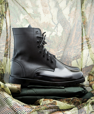 uniform green shoe: soldier uniform and black combat boot shoe on green background