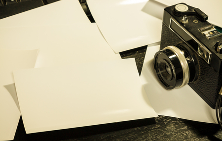 vintage camera and blank photograph on working desk Stock Photo