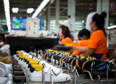 worker making sportshoe in footwear production line