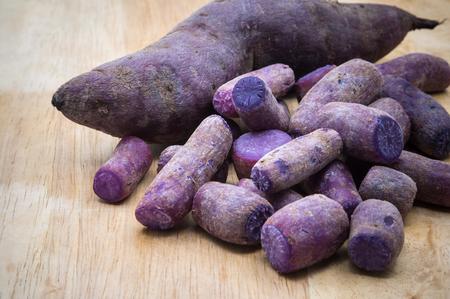 sweet purple potatoes on wood cutting board background Stock Photo