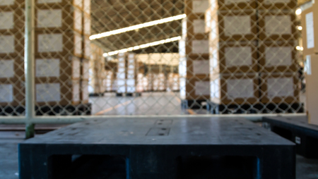 soft focus of empty black pallet in warehouse with stack of cartons background