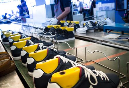 worker making shoe in production line of footwear industry