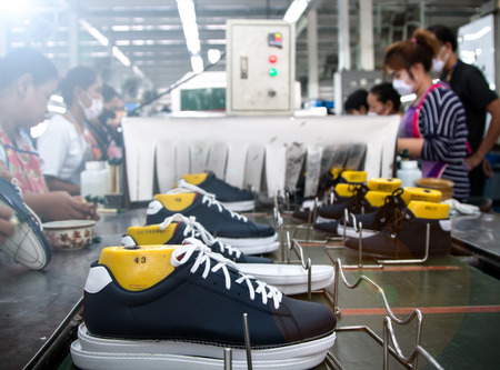 worker making shoe in production line of footwear industry with lens flare effect