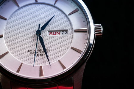 closeup of silver wristwatch display on black background