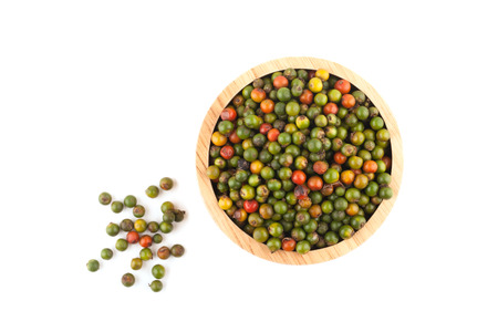 top view of fresh peppercorns in wooden bowl on white background