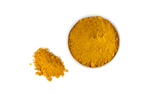 peppery: top view of turmeric powder in white ceramic bowl isolated on white background