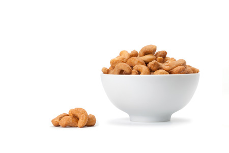 Front view of salted cashew nuts in white ceramic bowl isolated on white background with soft shadow