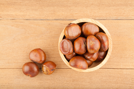 Top view angle of chestnut in wooden bowl on wood background