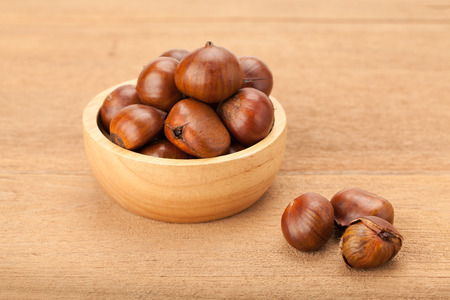 chestnut in wooden bowl on wood background Фото со стока