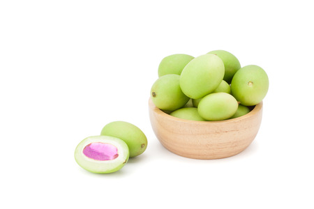Plum Mango or Marian Plum fruits (Bouea macrophylla Griffith) in wooden bowl isolated on white background with clipping path and soft shadow Фото со стока