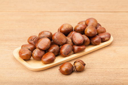 chestnut in wooden plate on wood background Фото со стока