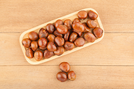 Top view angle of chestnut in wooden plate on wood background Фото со стока