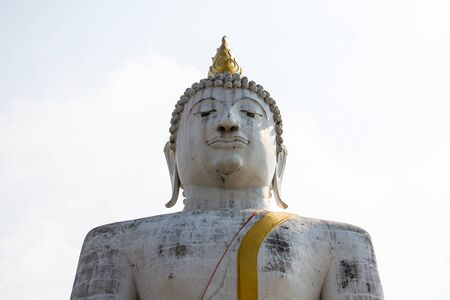 legs crossed at knee: Meditation front view of a large Buddha statue white