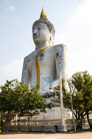 legs crossed on knee: Big Buddha in a temple courtyard in the heart of Thailand