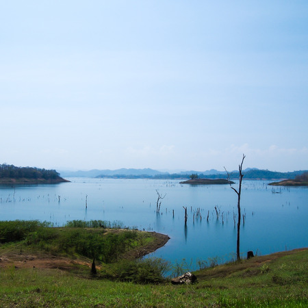 dyke: image of blue lake , mountains and dead trees of the dam Stock Photo
