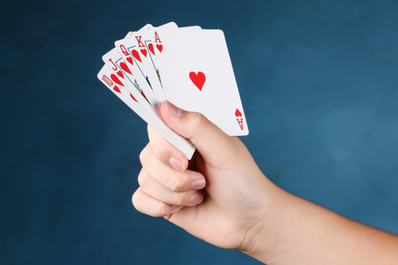 straight flush: A royal straight flush playing cards poker in hand in hearts