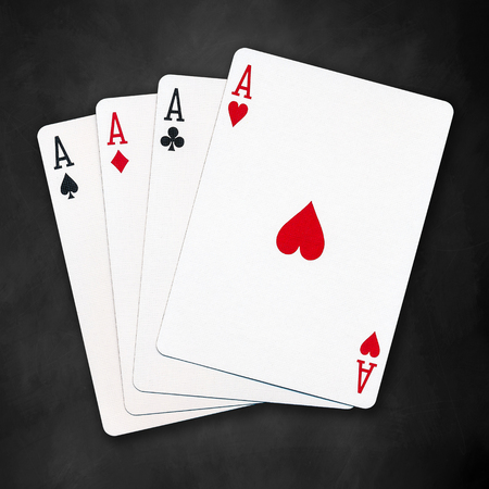 four objects: A winning poker hand of four aces playing cards suits on black background