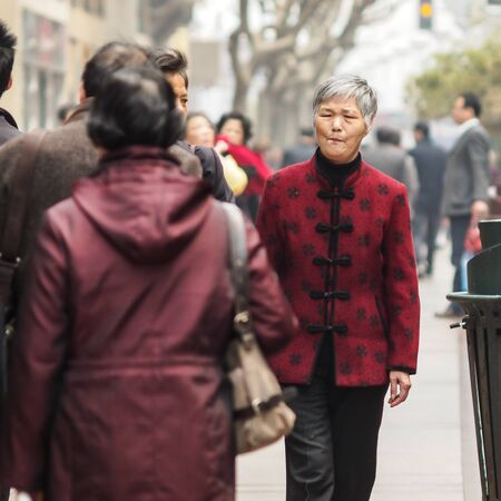 solicitude: SHIANGHAI, CHINA - April 8, 2011 : Old Chinese woman with red traditional shirt walking at walk street in Shianghai. Editorial