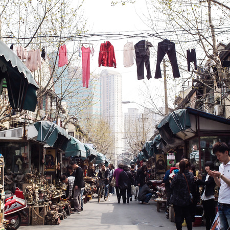 old items: SHANGHAI, CHINA - April 9, 2011 : Amazing view of old town area in Shanghai, There are clothes lines across over the flea market