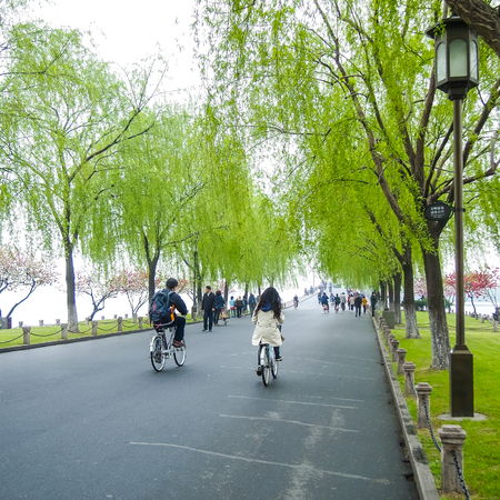 HANGZHOU, CHINA - April 13, 2011 : View in the mist of Xihu, the west lake in hangzhou china, this is image of Chinese couple cycling ,ride the bike in the park