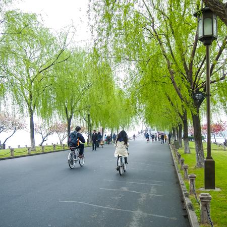 HANGZHOU, CHINA - 13 april 2011: Uitzicht in de mist van Xihu, het westen meer in Hangzhou China, dit is het beeld van het Chinese paar fietsen, rijden de fiets in het park
