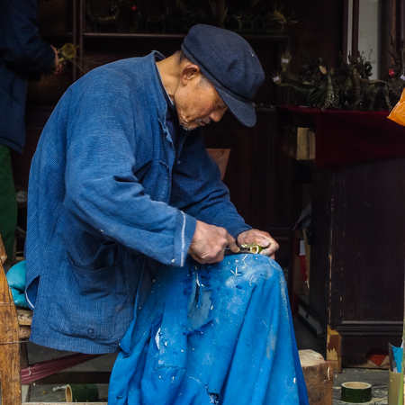 11 year old: ZHOUZHUANG, SHANGHAI - April 11, 2011 : Zhouzhuang, the ancient water village is Shanghai tourist attraction with 1,000,000 visitors per year and there are a lot of variety activities have done here, in this image, the old Craftman is working