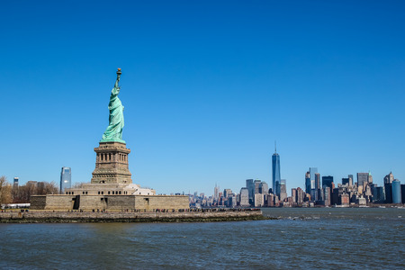Statue of Liberty on a sunny day, Manhattan in the background.