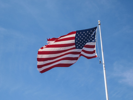 Tattered American Flag in the blue sky Stock Photo