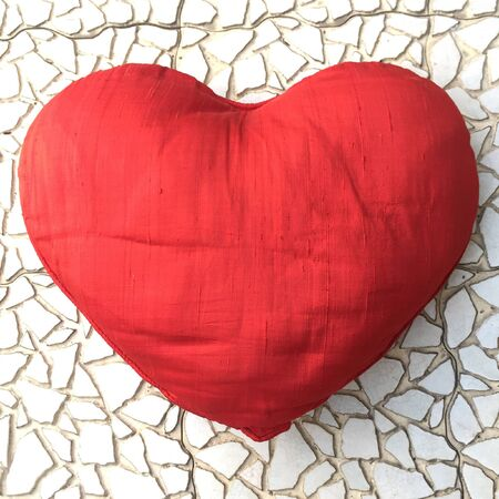 It is a cute red cushion on the mosaic floor. Stockfoto