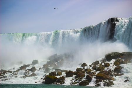 American side of the beautiful Niagara falls, New York, USA. View from the boat in the river.