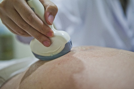 Obstetrician examining pregnant belly by ultrasonic scan. Stock Photo - 11810866