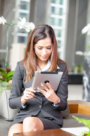 Portrait of a young businesswoman working with tablet at the hotel lobby  photo
