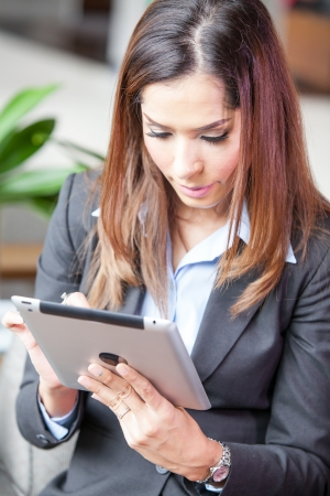 Portrait of a young businesswoman working with tablet at the hotel lobby