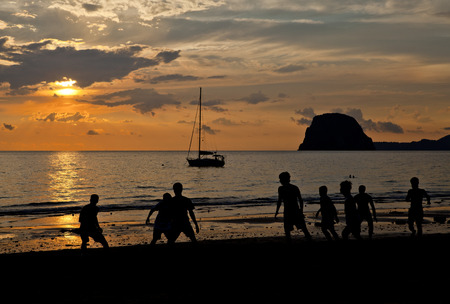 scorching: People play football on the beach   Stock Photo