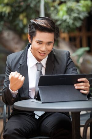 Success businessman looking data on tablet.