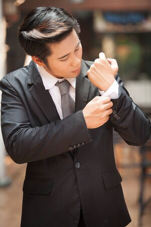 correcting: Closeup of a man in black suit correcting a sleeve.