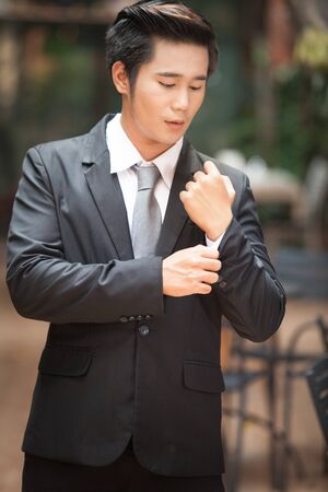 Closeup of a man in black suit correcting a sleeve.