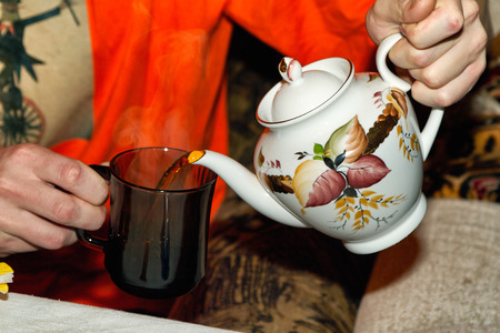 Photo of hands with tea cup. Man pours hot tea into a cup from a teapot