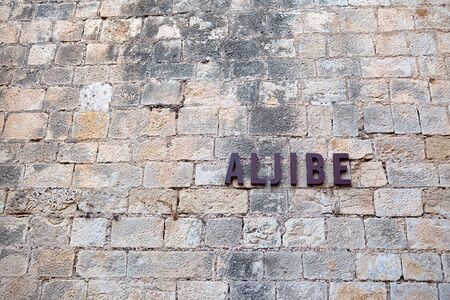 dilapidated wall: the inscription on an ancient stone wall of Santa Barbara castle. Alicante, Spain. Stock Photo