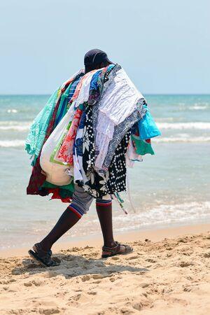 illegal seller of fabrics, dresses, glasses, walks on the beach Stock Photo