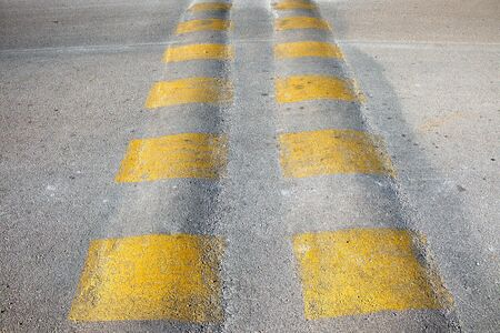Dual speed bump with yellow stripes on the road. Algorfa, Spain.