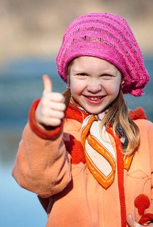 Little beautiful smiling girl in pink coat raises her fingers up against the background of a lake.
