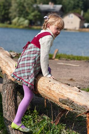 A little girl in a dress plays near a fallen tree near a lake. Stock Photo