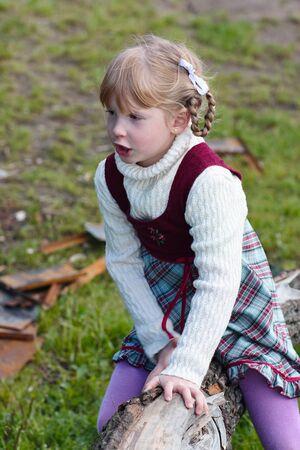 A little girl in a dress plays near a fallen tree near a lake. Stock Photo